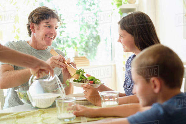 Children (8-9, 10-11) eating salad with parents Royalty-free stock photo