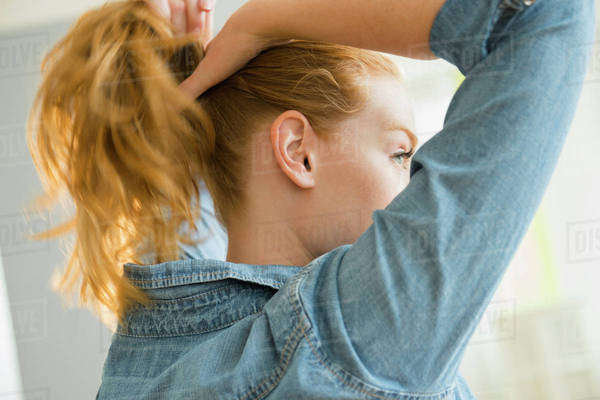 Young woman tying hair Royalty-free stock photo