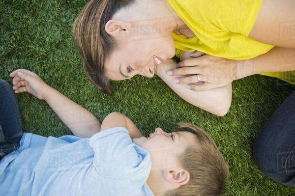 Mother and son (6-7) relaxing on grass Royalty-free stock photo