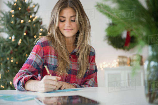 Young woman sitting at table and writing Royalty-free stock photo