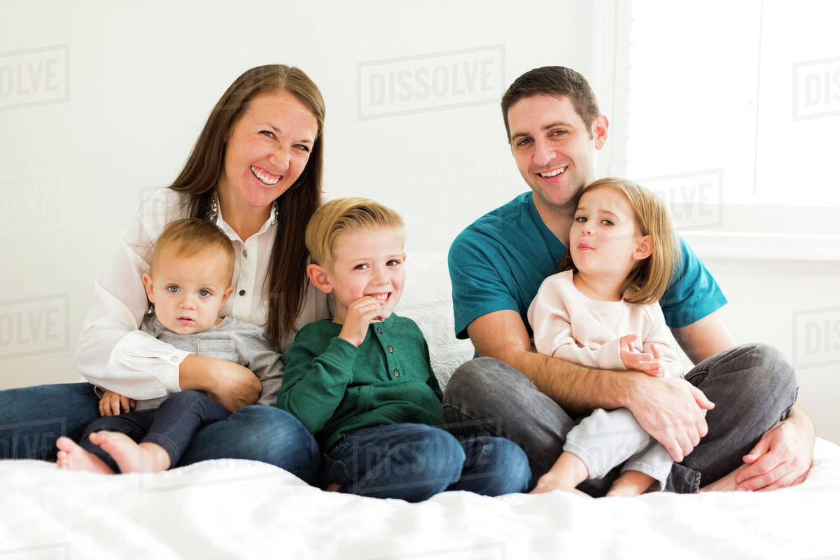 Portrait of family with three children (2-3, 4-5) sitting on bed