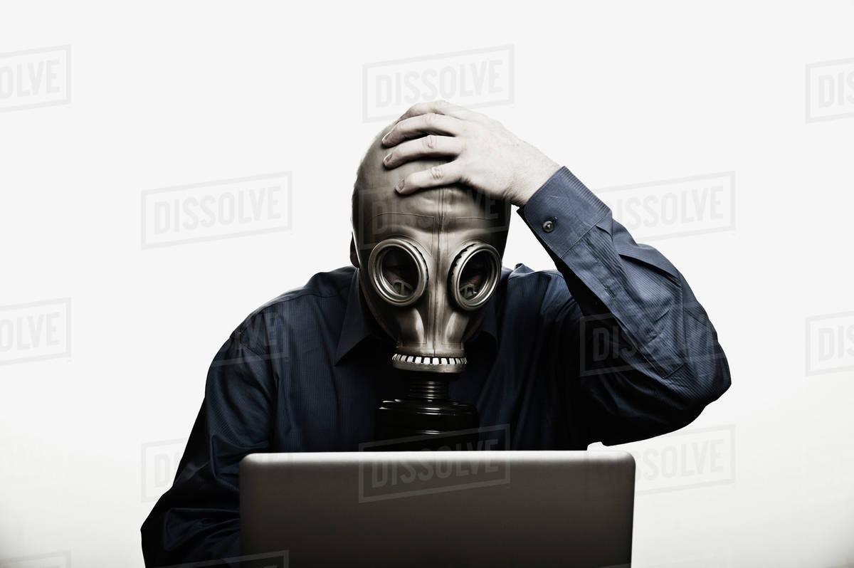 Studio shot of man in front of laptop wearing gas mask - Stock Photo -  Dissolve