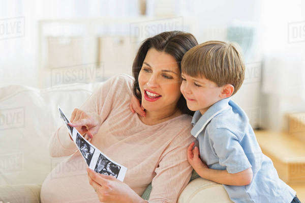 Pregnant woman with son (4-5) looking at ultrasound photo Royalty-free stock photo