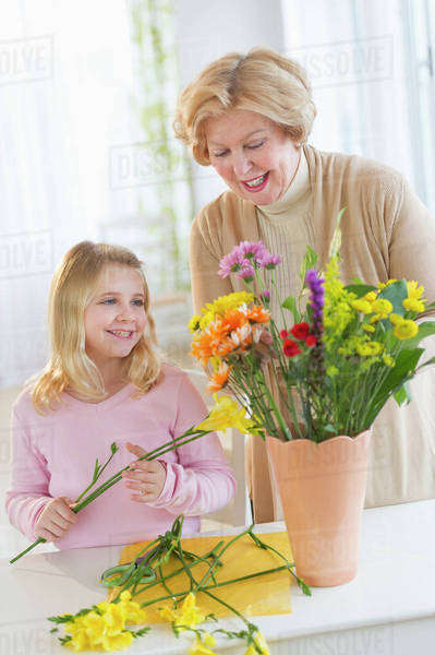 Smiling senior woman arranging flowers with granddaughter (8-9) Royalty-free stock photo