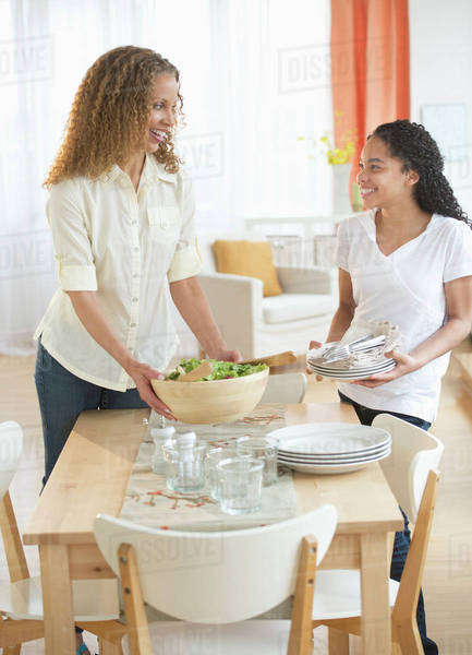 Mother with daughter (10-11) setting table Royalty-free stock photo