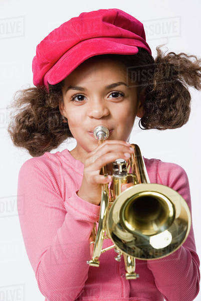 Portrait of girl (8-9) playing trumpet, studio shot Royalty-free stock photo