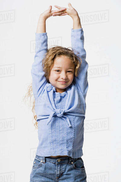 Studio portrait of smiling girl (8-9) with arms up Royalty-free stock photo