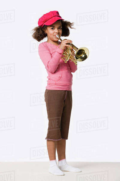 Studio portrait of girl (8-9) playing trumpet Royalty-free stock photo