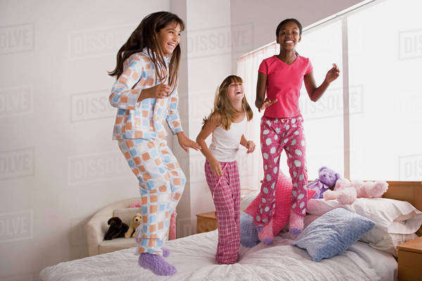 Three girls (10-11) jumping on bed at slumber party Royalty-free stock photo