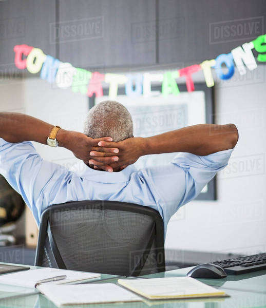 Rear view of man in office, congratulations sign in background Royalty-free stock photo