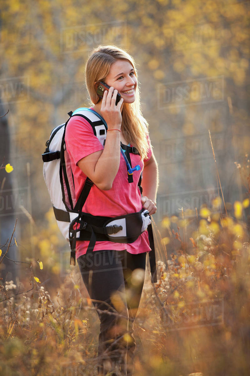 USA, Utah, young woman hiking in forest and talking on mobile phone Royalty-free stock photo