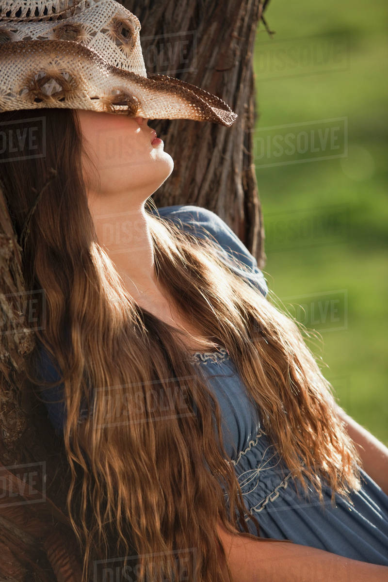 f7d986e2819 Cowgirl leaning against tree with her hat covering her face - Stock ...