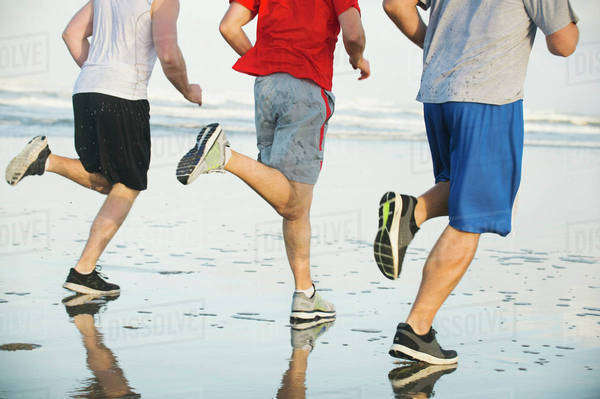 Men running on beach Royalty-free stock photo