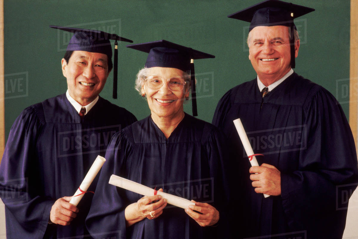Three adult students wearing graduation gowns - Stock Photo - Dissolve
