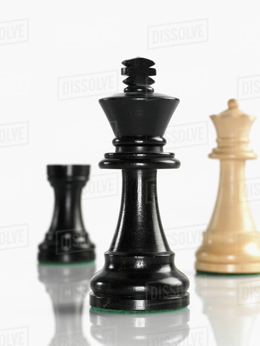 King chess piece with queen and rook in background stock photo
