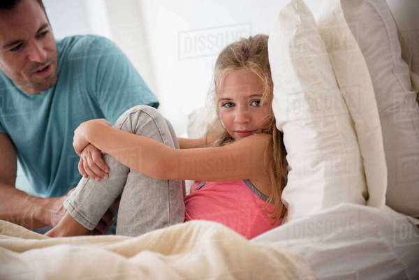 Father talking to daughter (6-7) in bedroom Royalty-free stock photo