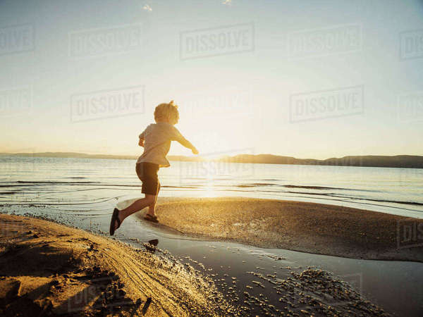 Small boy (4-5) jumping over water on sunny day Royalty-free stock photo