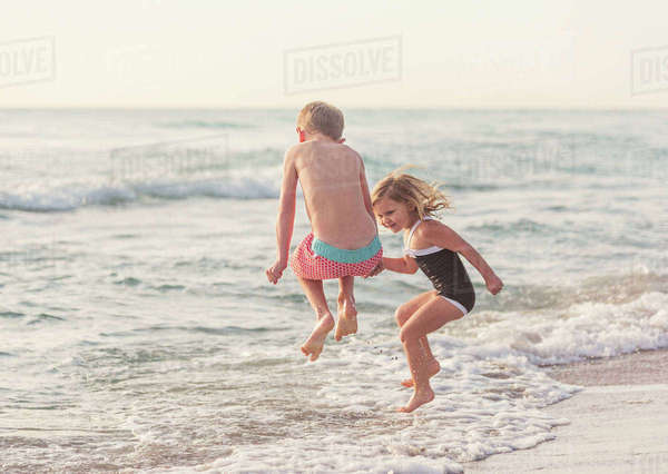 Boy (6-7) and girl (4-5) jumping in water on beach Royalty-free stock photo