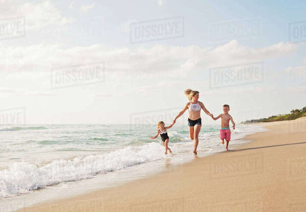 Mother running with boy (6-7) and girl (4-5) on beach by water Royalty-free stock photo