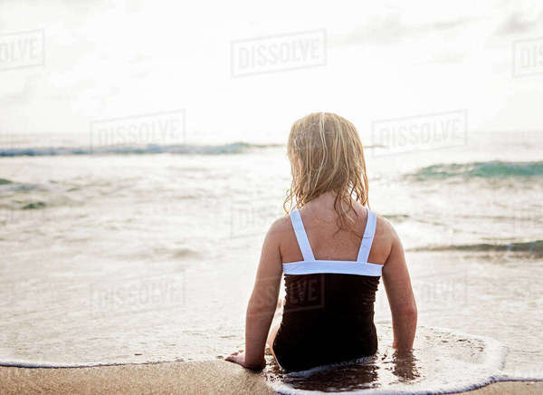 Girl (4-5) lying down in water on beach Royalty-free stock photo