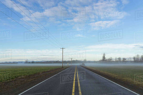 Highway going through plain covered with fog Royalty-free stock photo