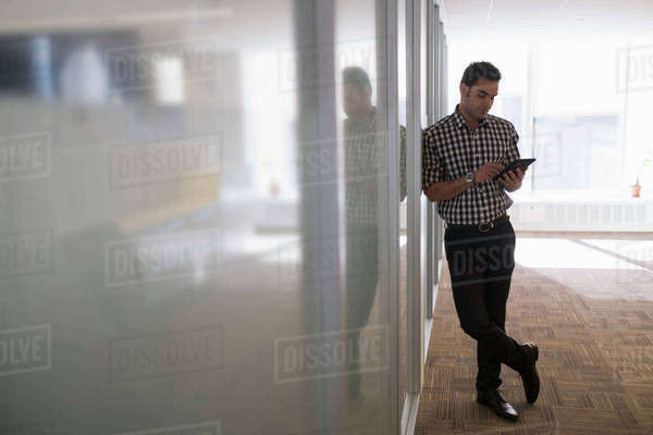 Young man standing in corridor with digital tablet Royalty-free stock photo