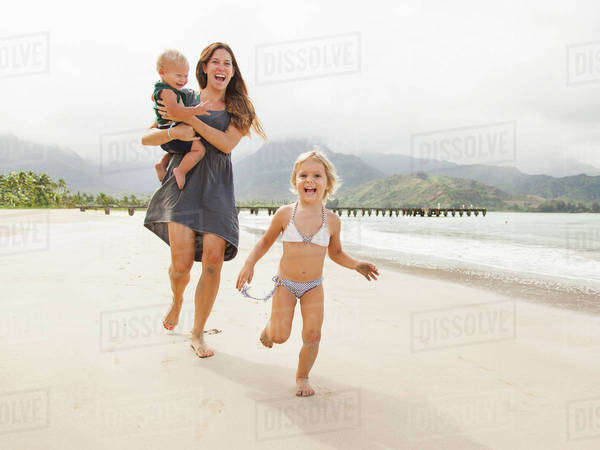 Mother with daughters (6-11 months, 2-3) on beach Royalty-free stock photo