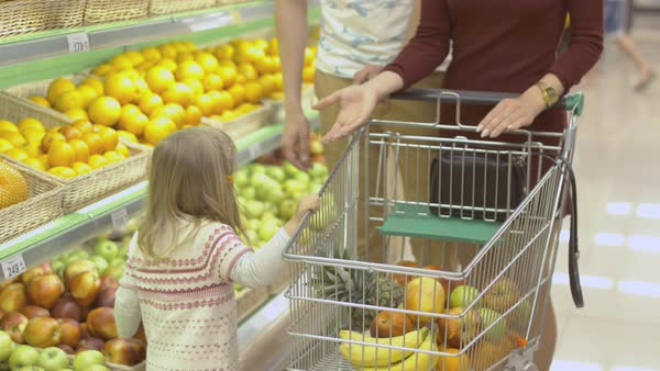 Family makes purchases in the supermarket. Little girl putting apples in the trolley Royalty-free stock video