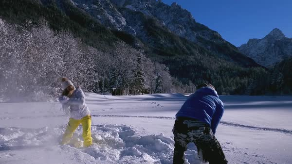 Couple having a snowball fight in a field. Man tosses woman into the snow during playful activity  Royalty-free stock video