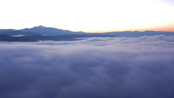 Aerial - Mountain silhouette above the clouds at sunset Royalty-free stock video