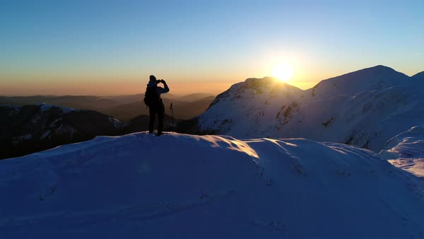 Aerial - Male mountaineer standing on top of snowy mountain and taking photos of beautiful winter scenery with his phone at sunset Royalty-free stock video
