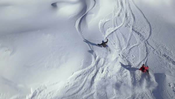 Slow motion - Aerial shot of two skiers riding in powder snow Royalty-free stock video