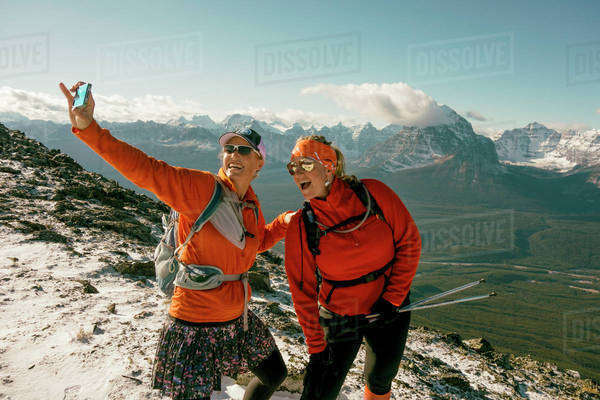 Female hikers take smartphone picture of themselves in the mountains. Royalty-free stock photo