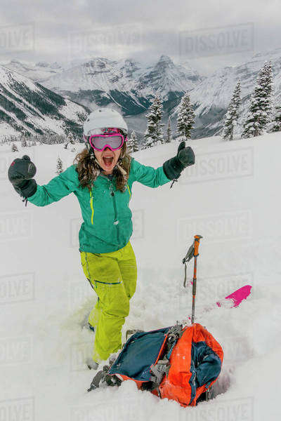 Female ski adventurer gives the thumbs up before starting a ski run in the backcountry. Royalty-free stock photo