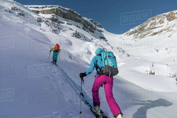 Two female ski adventurers ascend a steep snow slope in the alpine. Royalty-free stock photo