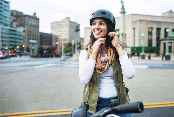 Woman wearing helmet while standing with bicycle in city Royalty-free stock photo