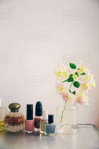 Beauty Products Arranged By Flower Vase On Table Against White Wall