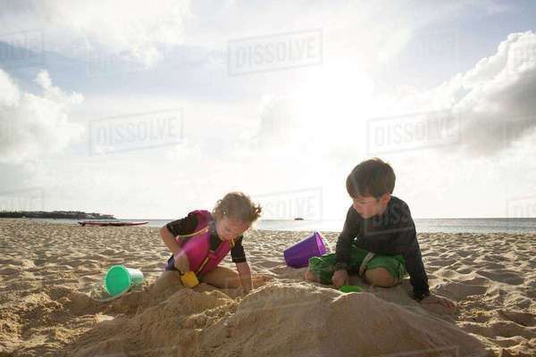 Siblings playing with sand at beach against sky Royalty-free stock photo