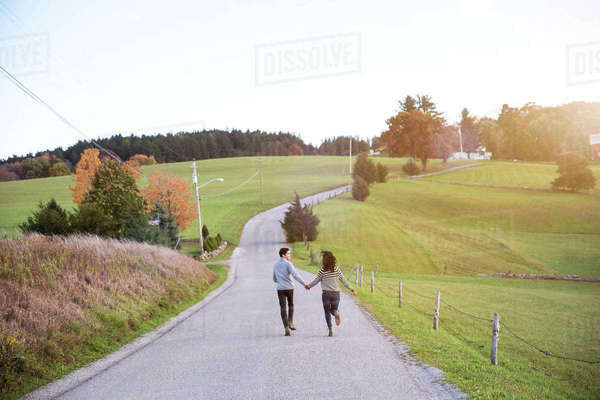 Playful couple running on footpath against sky Royalty-free stock photo