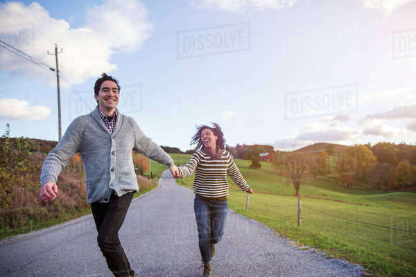 Cheerful couple running on footpath against sky Royalty-free stock photo