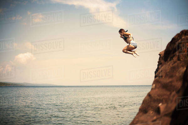 Young girl jumping off cliff into water Royalty-free stock photo