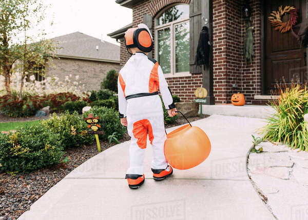 Rear view of boy in Halloween costume with container walking in yard Royalty-free stock photo