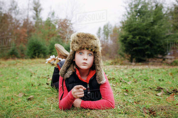 Portrait of girl in hunters cap gesturing while lying on field Royalty-free stock photo