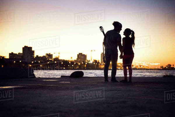 Silhouette couple standing at lakeshore against clear sky during sunset Royalty-free stock photo