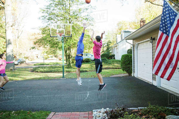Senior man playing basketball with grandson at backyard Royalty-free stock photo
