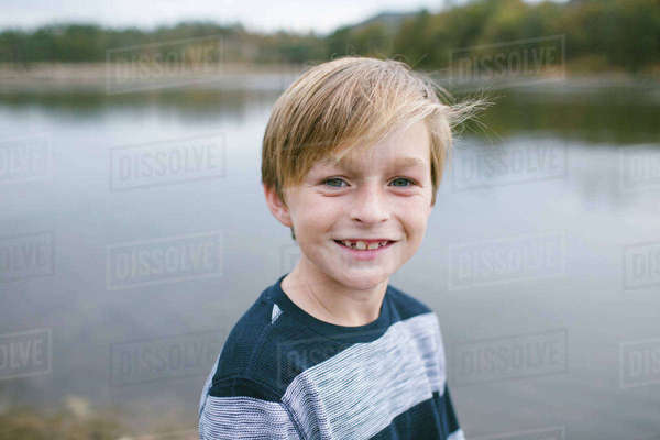 Portrait of smiling boy standing against lake Royalty-free stock photo