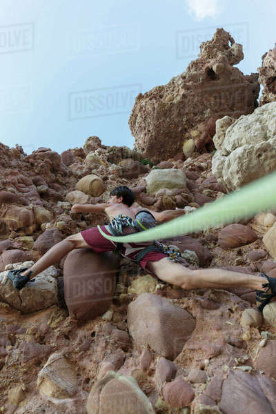 Low angle view of hiker climbing rock against sky Royalty-free stock photo