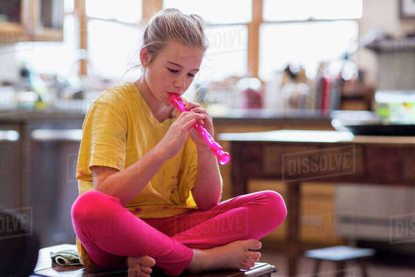 Girl playing flute while sitting on table at home Royalty-free stock photo