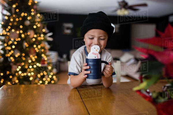 Happy boy holding cup with marshmallow snowman at table in home Royalty-free stock photo