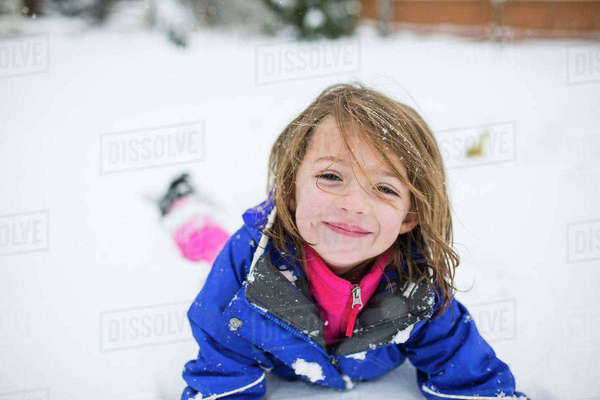 Portrait of cute girl lying on snow covered field Royalty-free stock photo